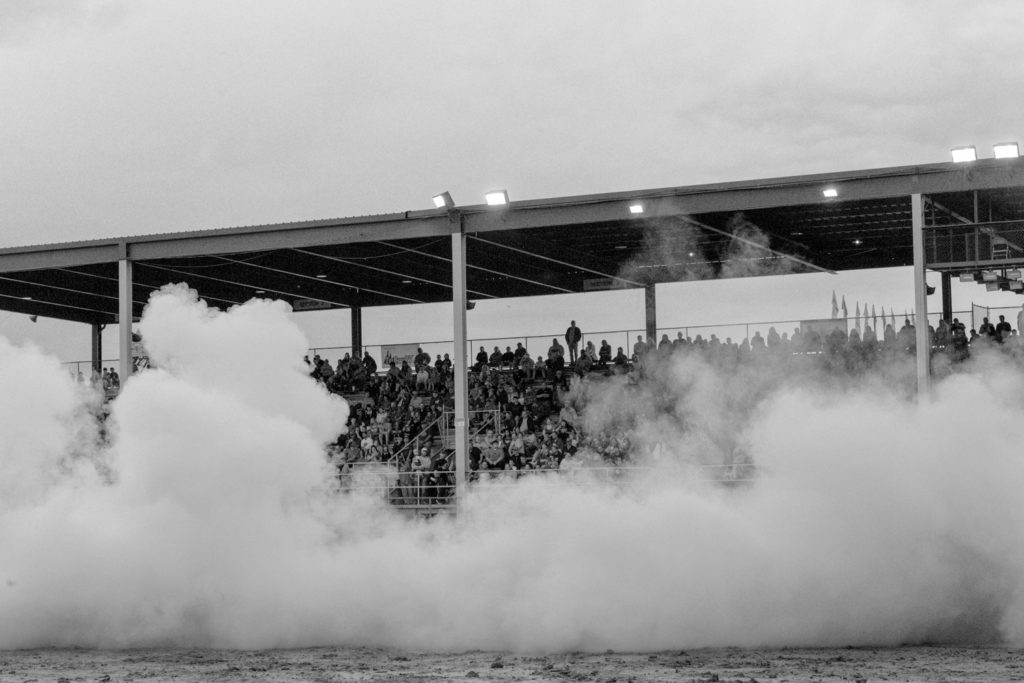 Midland, Michigan, USA. Midland County fair. The smoke produced by a car, during a bornout competition. In the background the spectators on the grandstands of the track.