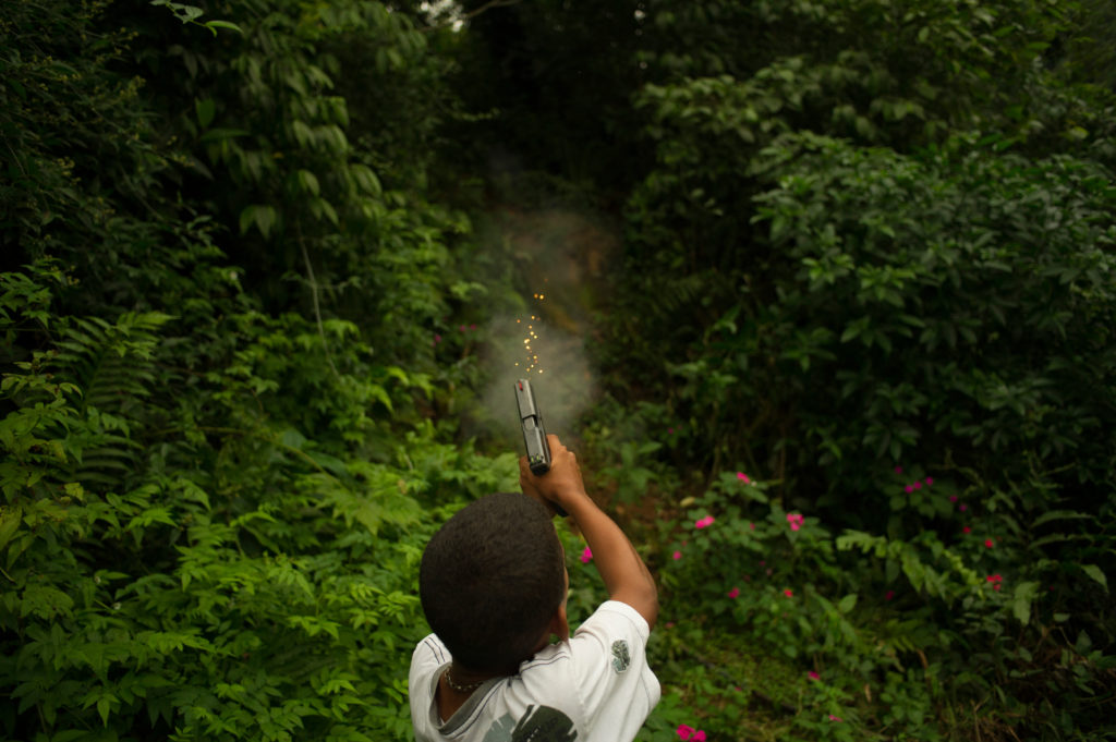 A 11 years old boy, member of an armed criminal faction in São Paulo Brazil, training shooting with an 9mm automatic hand gun.