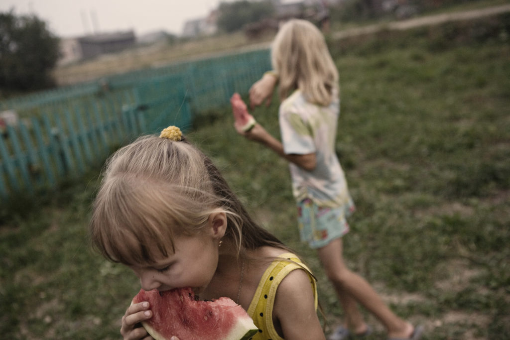 In short Russian summers, life takes place outside. Here, children eat watermelon in the afternoon in Tonshaevo village. Mari-El Republic. Russia. 2011.