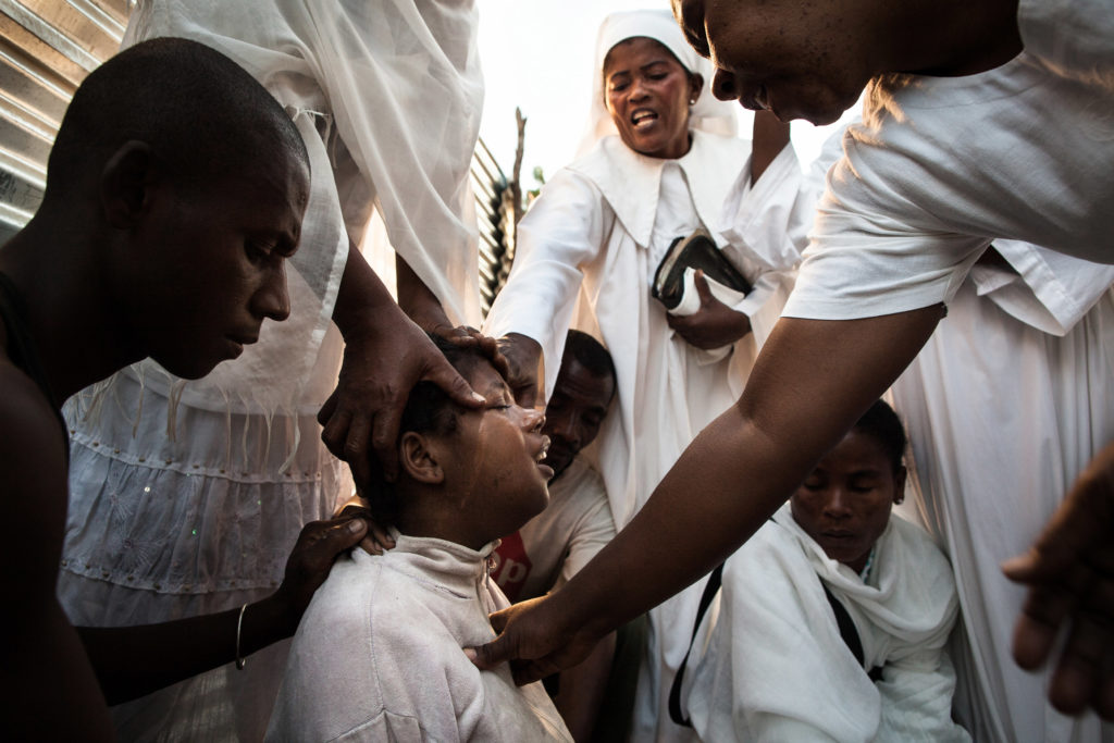 The exorcism of a 13 years old new mother, crying and sceraming while being held by five exorcist and her older husband. (Madagascar - Toliara city - Toby Betela)